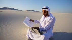 Muslimskt sammanträde för arkitekt för arabUAE-shejk med bärbara datorn på sand i öken på varm sommardag stock video