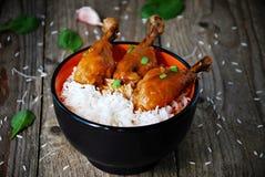 Muslos anaranjados del pollo con el arroz blanco en cuenco Imagenes de archivo