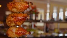 Muslos asados del pollo en el filete del rotisserie imagen de archivo