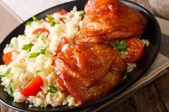 Muslos rubicundos deliciosos del pollo con un adorno del arroz con el veget Foto de archivo libre de regalías