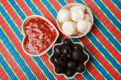 Mussarela do queijo, azeitonas pretas e molho de tomate em um fundo multi-colorido imagens de stock