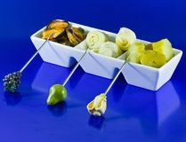 Mussels, artichokes and gherkins on blue backgroun Royalty Free Stock Image