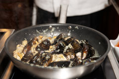 Mussels being fried in pan Royalty Free Stock Image