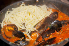 Mussels being fried with tomato sauce and pasta Stock Photo