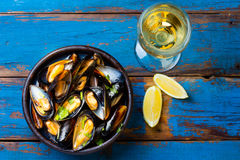 Mussels in clay bowl, glass of white wine and lemon. On wooden blue background Royalty Free Stock Images