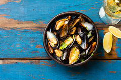 Mussels in clay bowl, glass of white wine and lemon. On wooden blue background Stock Photos