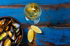 Mussels in clay bowl, glass of white wine and lemon. On wooden blue background Stock Image