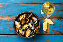 Mussels in clay bowl, glass of white wine and lemon. On wooden blue background Royalty Free Stock Photo