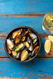 Mussels in clay bowl, glass of white wine and lemon Stock Image
