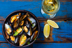Mussels in clay bowl, glass of white wine and lemon. On wooden blue background Royalty Free Stock Photos