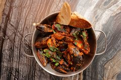 Mussels cooked with arrabiata sauce and served in metal pot Stock Image