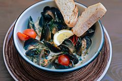 Mussels dish with some bread and little tomatoes. Mussels dish. Close up of nice delicious mussels dish with some bread and little tomatoes in creamy sauce Royalty Free Stock Photography