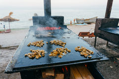 Mussels and fish frying at beach Royalty Free Stock Images