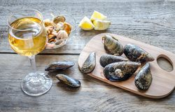 Mussels with a glass of white wine on the wooden table Royalty Free Stock Photography