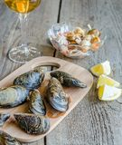 Mussels with a glass of white wine on the wooden table Stock Images