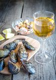 Mussels with a glass of white wine on the wooden table Stock Photo