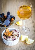 Mussels with a glass of white wine on the wooden table Royalty Free Stock Photo