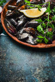 Mussels with lemon and ingredients for cooking in wooden plate on rustic background, top view Royalty Free Stock Images