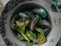 Mussels and mint leaves in casserole. Street food in the market Royalty Free Stock Photos