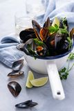 Mussels with parsley and lemon on a light gray background with copy space. Seafood stock photo