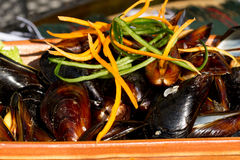 Mussels on the plate. Delicious dish with mussels and carrot Royalty Free Stock Images