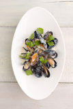 Mussels in a plate on white wooden background. Moules Marinieres - Mussels cooked with white wine, cream sauce on white wooden background Royalty Free Stock Photo