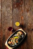 Mussels and shrimp in black pan cooking dish on dark wooden background Royalty Free Stock Images