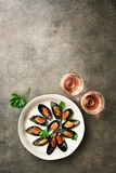 Mussels with spices, parsley and two glasses of pink sparkling wine, dark rustic background. Top view, flat lay, copy space