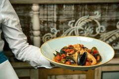 Mussels with tomato and olives - delicious and healthy dinner in a restaurant. A plate of seafood in male hands closeup waiter. Mussels with tomato - delicious Royalty Free Stock Images