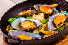 Mussels with vegetables in black pot Royalty Free Stock Images
