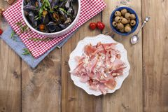 mussels w białym ceramicznym pucharze na czerwonej pielusze, Oliwki, chleb Mięso na talerzu Na drewnianym tle Bezpłatna przestrze Obraz Stock