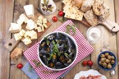 mussels w białym ceramicznym pucharze na czerwonej pielusze, Ser na drewnianej desce i szkło biały wino, oliwki, chleb Mięso na a Obraz Royalty Free
