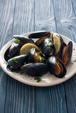 Mussels on white plate over blue wood background Stock Photography