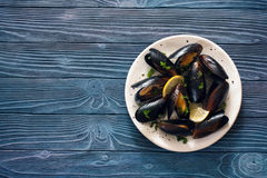 Mussels on white plate over blue wood background Stock Images