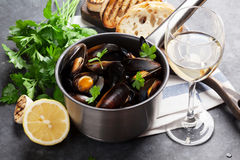 Mussels and wine. Mussels in copper pot and white wine on stone table royalty free stock photos
