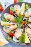 Mussels in the wings, baked with mozzarella, tomato and leek on a large round platter Mediterranean food Royalty Free Stock Photography