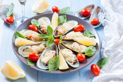 Mussels in the wings, baked with mozzarella, tomato and leek on a large round platter Mediterranean food Stock Photo