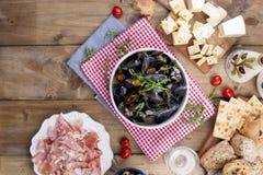 musselsin biały ceramiczny puchar na czerwonej pielusze, Ser na drewnianej desce i szkło biały wino, oliwki, chleb Mięso na a Fotografia Stock