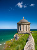 Mussenden Temple on butte, Northern Ireland. Stone Mussenden Temple on butte overlooking sea in Northern Ireland on sunny day against blue skies royalty free stock photos