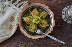 Musslan formade special turkisk baklava med pistaschen och turkiskt kaffe fotografering för bildbyråer