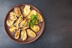 Musslor bakade med ost och kryddor i skalmusslor Citron PA Royaltyfri Foto
