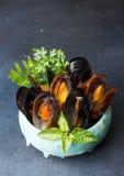 Musslor bakade med smör och persilja i blå keramisk bunke och s Royaltyfri Bild