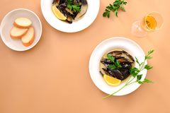 Musslor i krämig vitlök- och vinsås tjänade som med vitt vin Arkivbilder