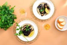 Musslor i krämig vitlök- och vinsås tjänade som med vitt vin Arkivbild