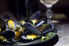 Musslor med exponeringsglas av vitt vin och timjan Arkivfoton