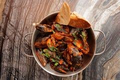 Musslor som lagas mat med arrabiatasås och tjänas som i metallkruka Fotografering för Bildbyråer