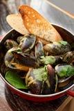 Musslor som lagas mat med curry och tjänas som i metallkrukan, asiatisk mat Arkivfoton