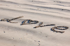 It Must Be Love. The word love wrote on a beach Royalty Free Stock Image