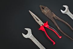 Must have at home used hand tools Combination Pliers, Needle Nose Pliers, wrench on black background. With copy space Royalty Free Stock Photography