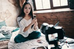 Must have thing. Beautiful young woman testing beauty product while making social media video stock photos